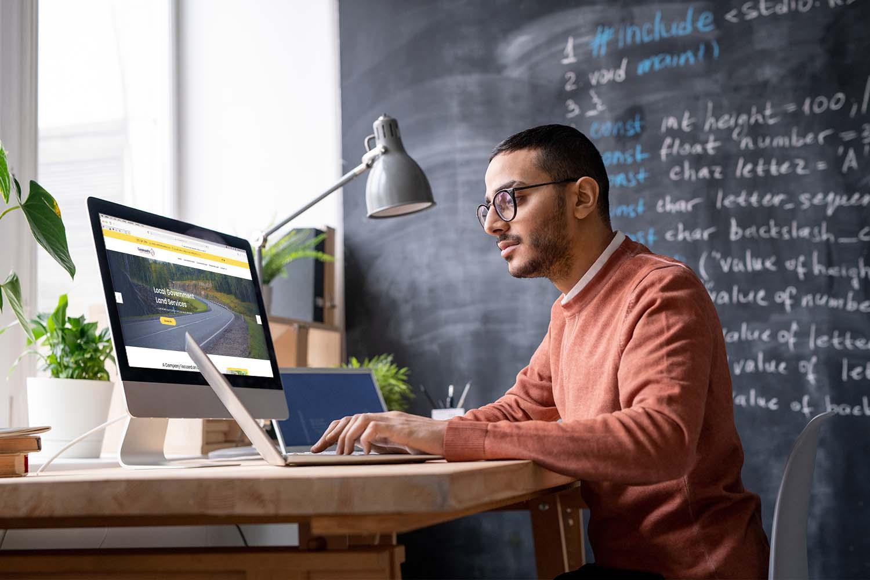 man on his laptop checking website, desktop near him, working on responsive website design